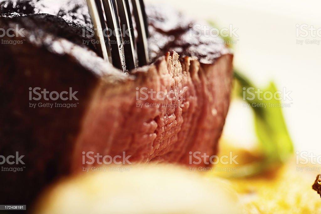 Juicy, medium-rare steak being sliced royalty-free stock photo