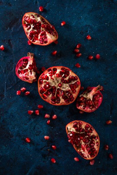 Juicy pomegranates on dark blue table. healthy food concept stock photo