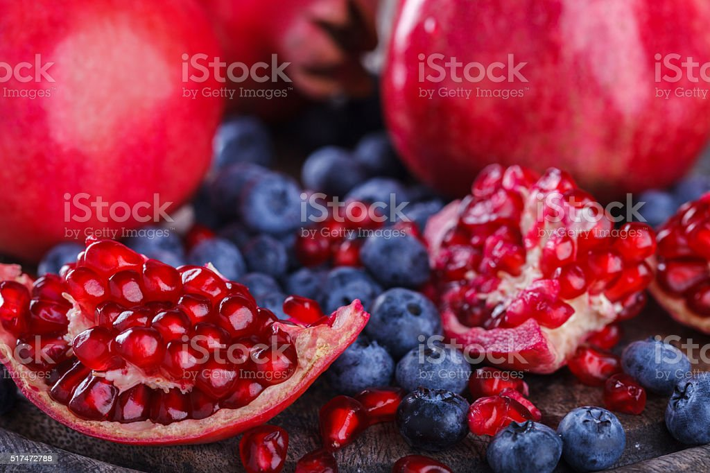 Juicy pomegranates,whole and broken and blueberries stock photo