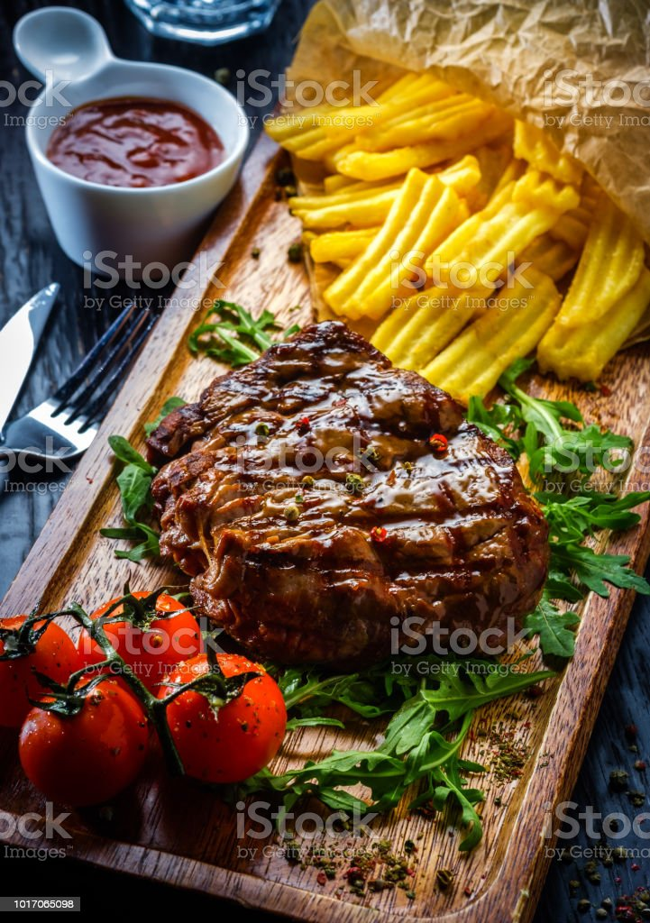 Juicy portions of grilled fillet steak served with tomatoes and roast vegetables on an old wooden board. стоковое фото