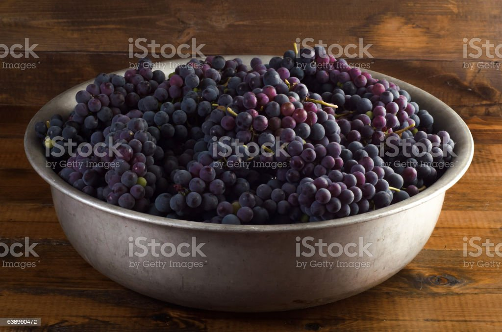 Juicy red grapes in bowl on wooden background stock photo