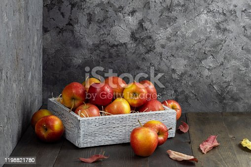 1020586746 istock photo Juicy ripe apples in a box on dark table 1198821780
