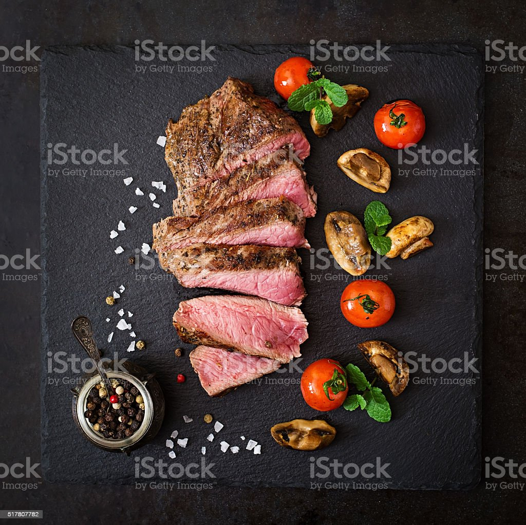 Juicy steak medium rare beef with spices and grilled vegetables. stock photo