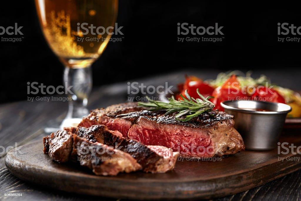 Sappige biefstuk medium zeldzame rundvlees met specerijen op houten bord op tafel foto