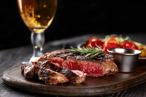 saftig stek medellång sällsynta biff med kryddor på träskiva på bord - biff bildbanksfoton och bilder