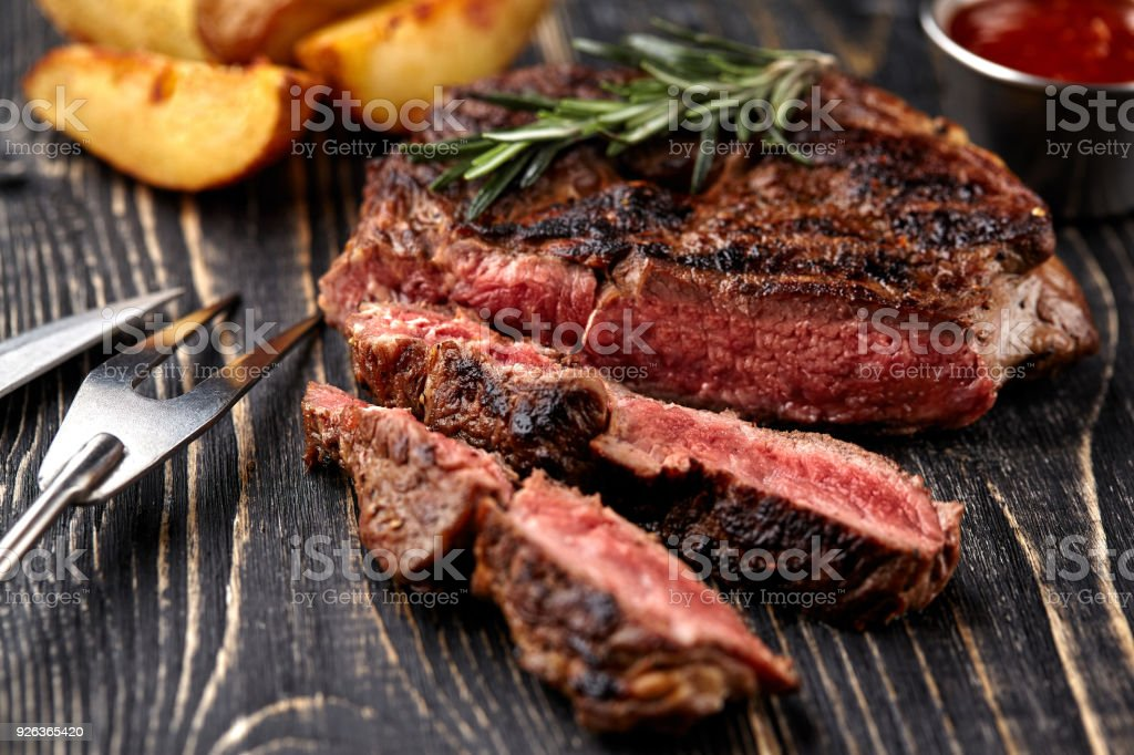 Juicy steak medium rare beef with spices on wooden board on table stock photo