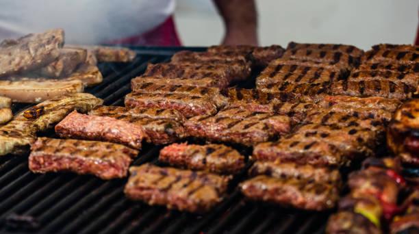 Saftiges dampfendes Fleisch auf einem Holzkohlegrill, Schweinesteaks, Hühnerbrust, Würstchen, Fleischkoteletts, rumänisches Hackfleisch (mici) bei einem Streetfood-Festival – Foto