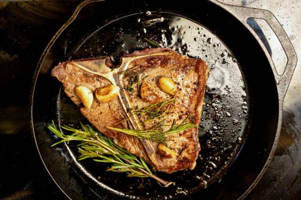 saftiges t-bone-steak rindfleisch in einer gusseisernen pfanne - steak anbraten stock-fotos und bilder