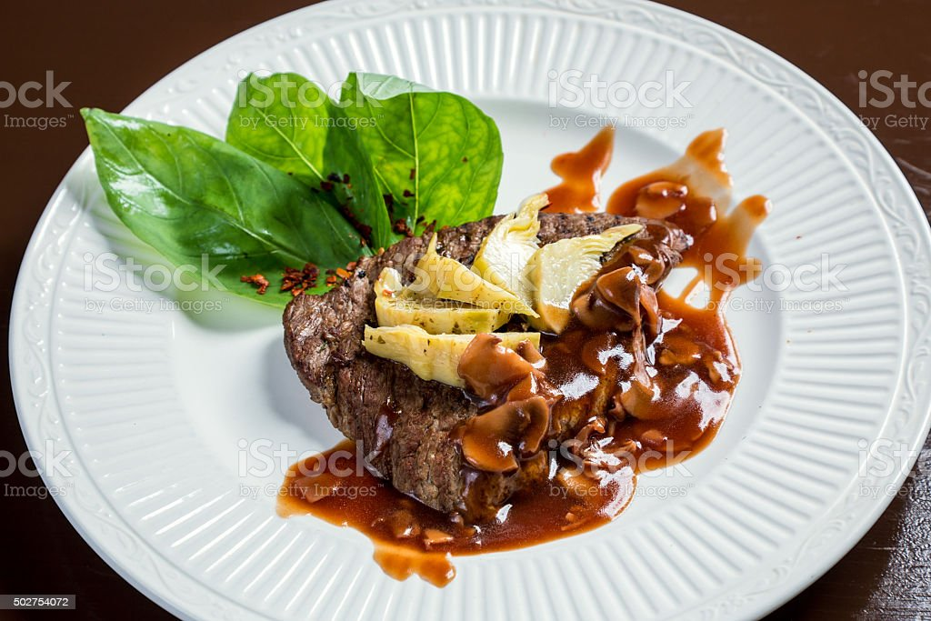 Juicy veal  steak with   artichokes stock photo
