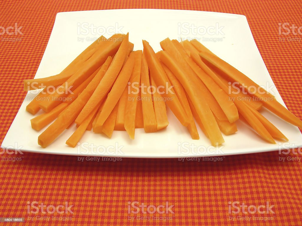 Julienne carrots on white plate and checked placemat stock photo