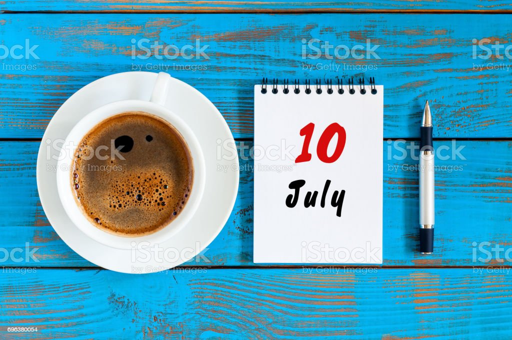 July 10th. Day 10 of month, calendar on blue wooden table background with morning coffee cup. Summer concept stock photo