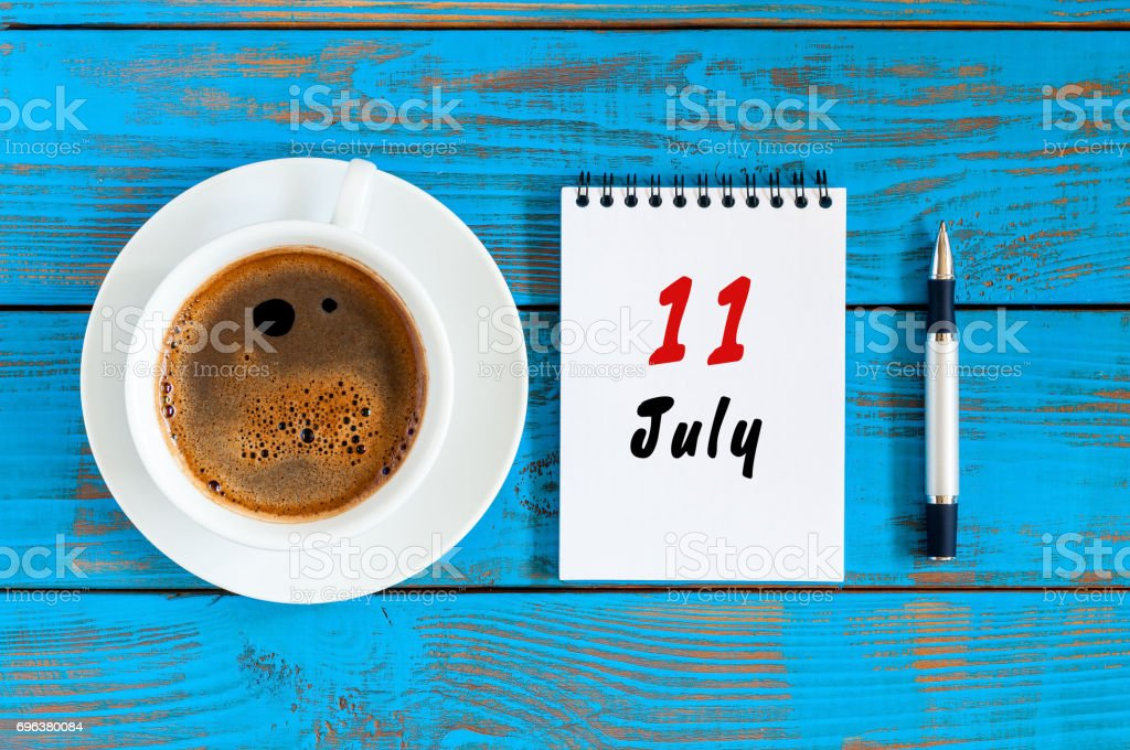 July 11th. Day 11 of month, calendar on blue wooden table background with morning coffee cup. Summer concept stock photo