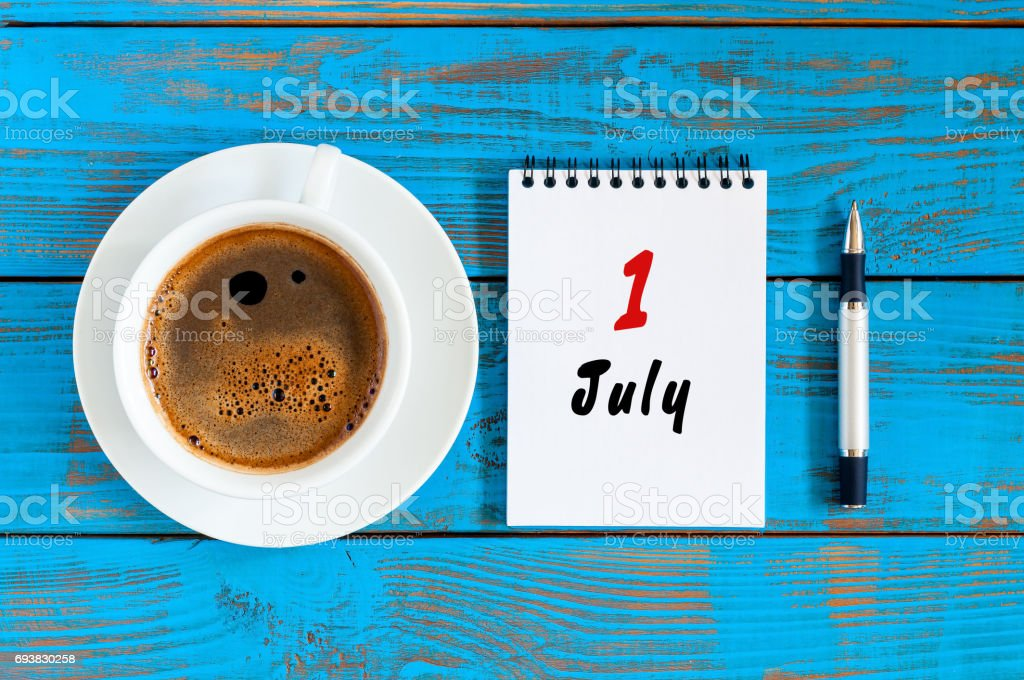July 1st. Day of the month 1 , calendar on business workplace background with morning coffee cup. Summer concept. Hello July stock photo