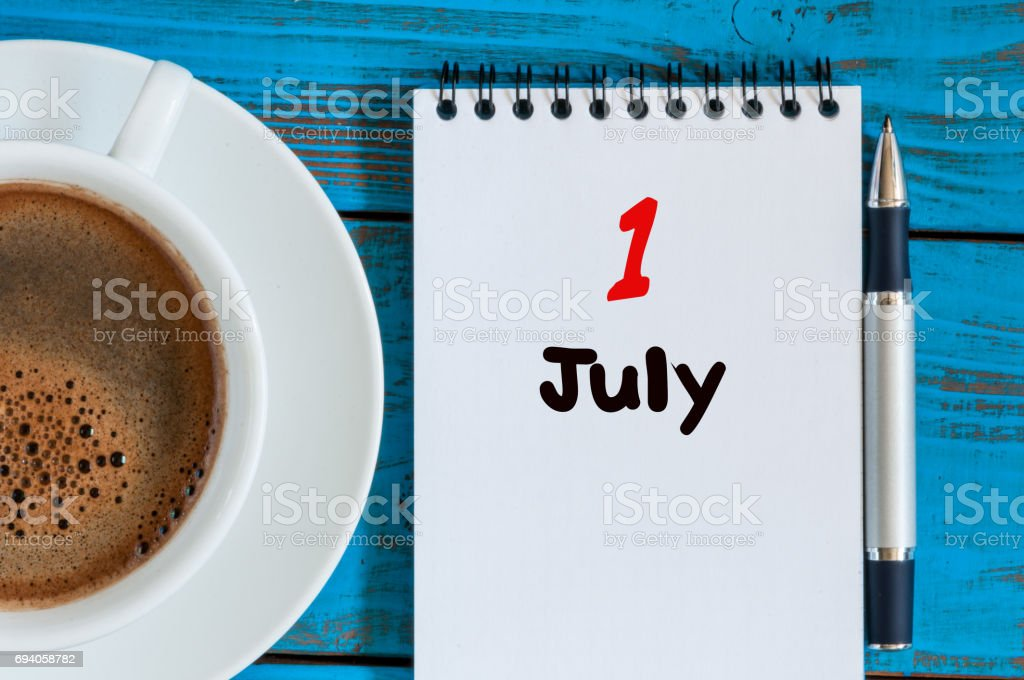 July 1st. Day of the month 1 , calendar on business workplace background with morning coffee cup. Summer concept. Empty space for text stock photo