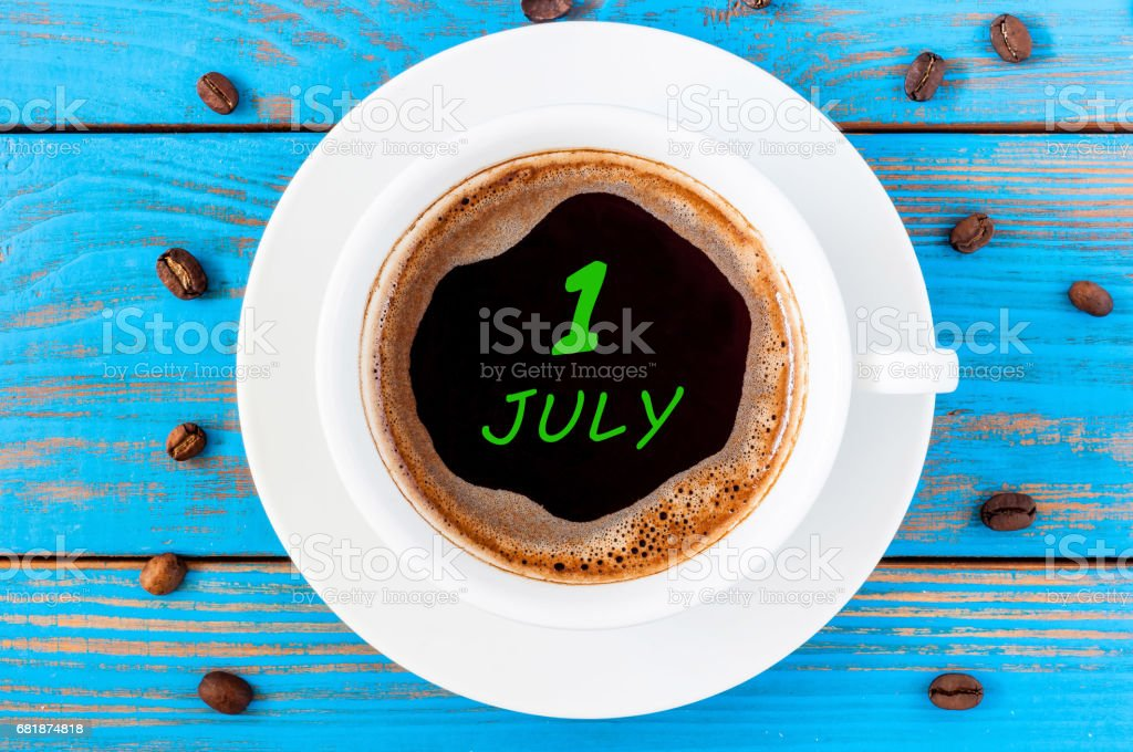 July 1st. Day of the month 1 , everyday calendar written on morning coffee cup at blue wooden background. Summer concept, Top view stock photo