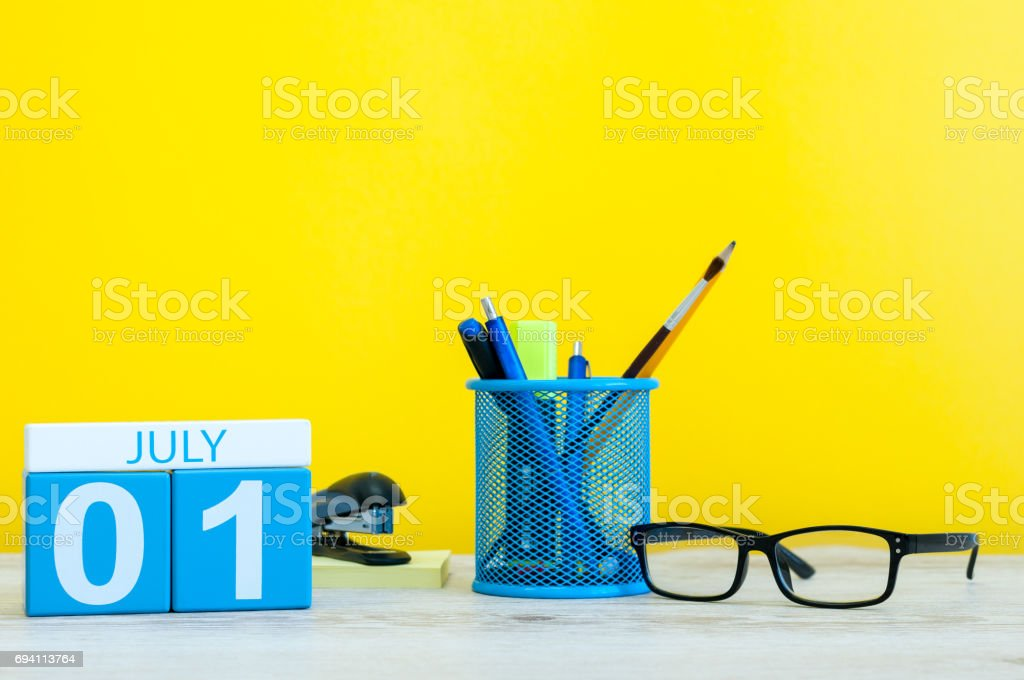 July 1st. Image of july 1, calendar on yellow background with office supplies. Summer time stock photo