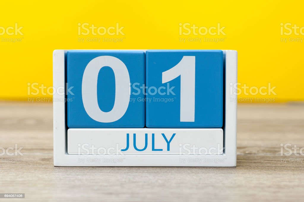 July 1st. Image of july 1, close-up wooden color calendar on yellow background. Summer day stock photo