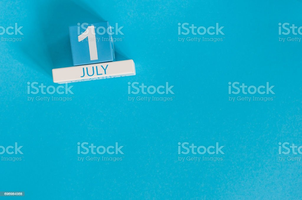 July 1st. Image of july 1 wooden color calendar on blue background. Summer day. Empty space for text stock photo