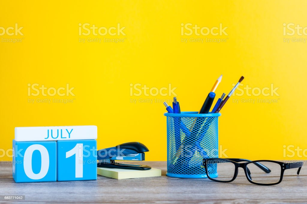 July 1st. Image of july 1 wooden color calendar on office suplies background. Summer day. Empty space for text stock photo