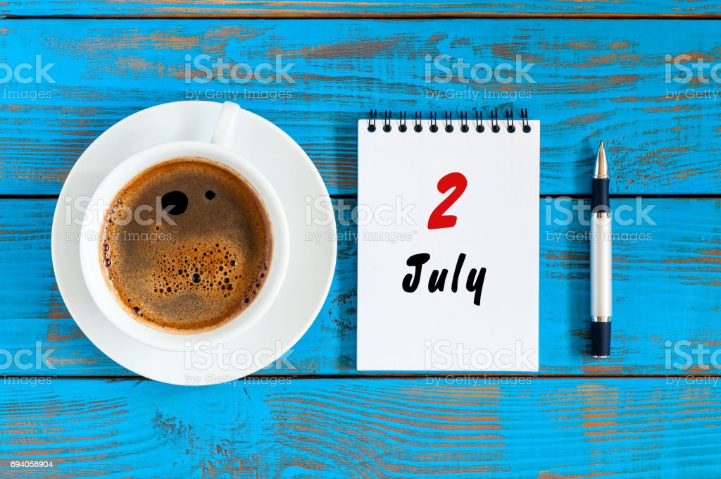 July 2nd. Day of the month 2 , calendar on blue wooden table background with morning coffee cup. Summer concept stock photo