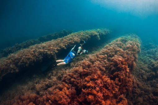istock July 30, 2019. Anapa, Russia. Underwater photographer with camera glides stones with seaweed in blue sea 1195379919