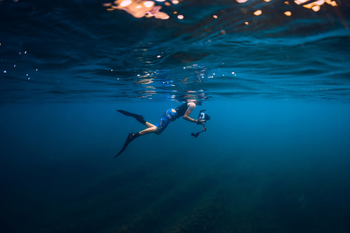 istock July 30, 2019. Anapa, Russia. Underwater photographer with camera swim in blue sea 1195379901