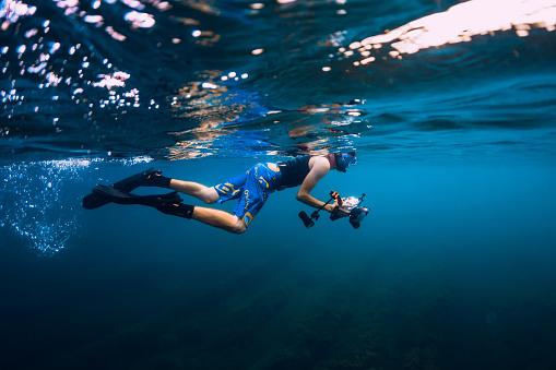 istock July 30, 2019. Anapa, Russia. Underwater photographer with camera swim in blue sea 1195379903
