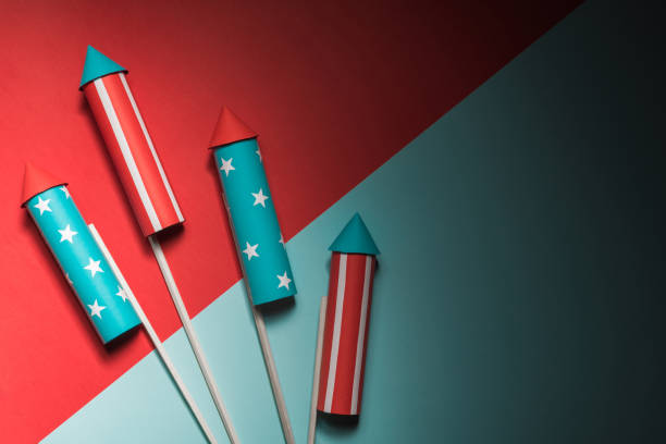 July 4, rockets for fireworks on a blue red background with space for text. in the style of minimalism stock photo