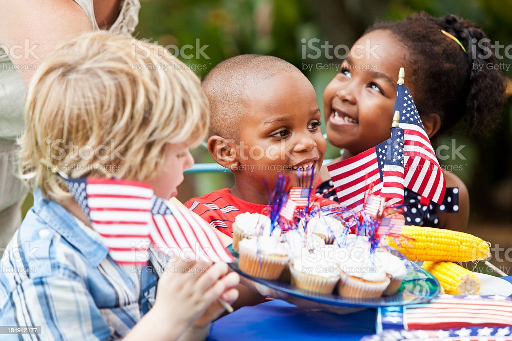 July 4th or Memorial Day picnic celebration Woman serving cupcakes to excited children (6, 4 and 7 years) at July 4th cookout.  Focus on boy in middle. 4-5 Years Stock Photo