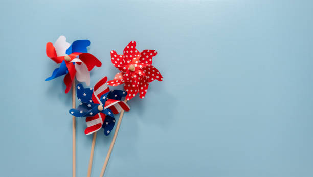 july 4th theme paper pinwheels on blue background. - july 4th stock pictures, royalty-free photos & images