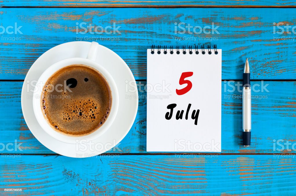 July 5th. Day of the month 5 , calendar on blue wooden table background with morning coffee cup. Summer concept stock photo