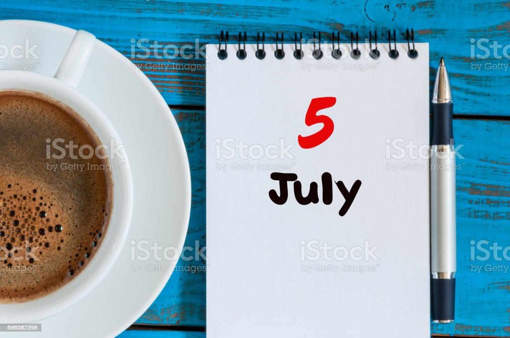 July 5th. Day of the month 5 , calendar on business workplace background with morning coffee cup. Summer concept. Empty space for text stock photo