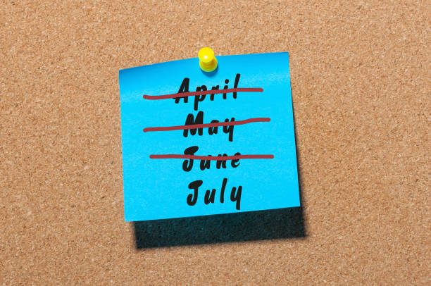 July beginning concept. Sticker with crossed out months April, May and June. Message at business corkboard stock photo