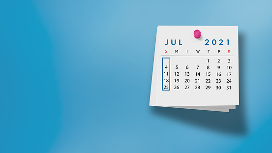 2021 July calendar on a white note paper pinned on wall against blue background. High resolution and copy space for all your crop needs.