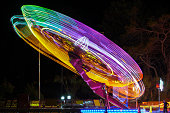 NIN, CROATIA -JULY.23.2020-Abstract, long exposure shot of spinning Children's vintage Carousel at an amusement park in the evening and night illumination\nD.H