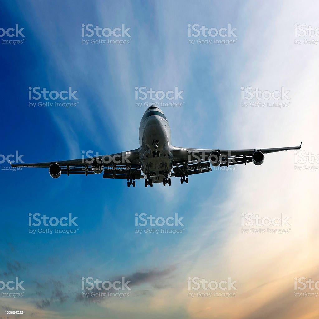 jumbo jet airplane landing at dusk royalty-free stock photo