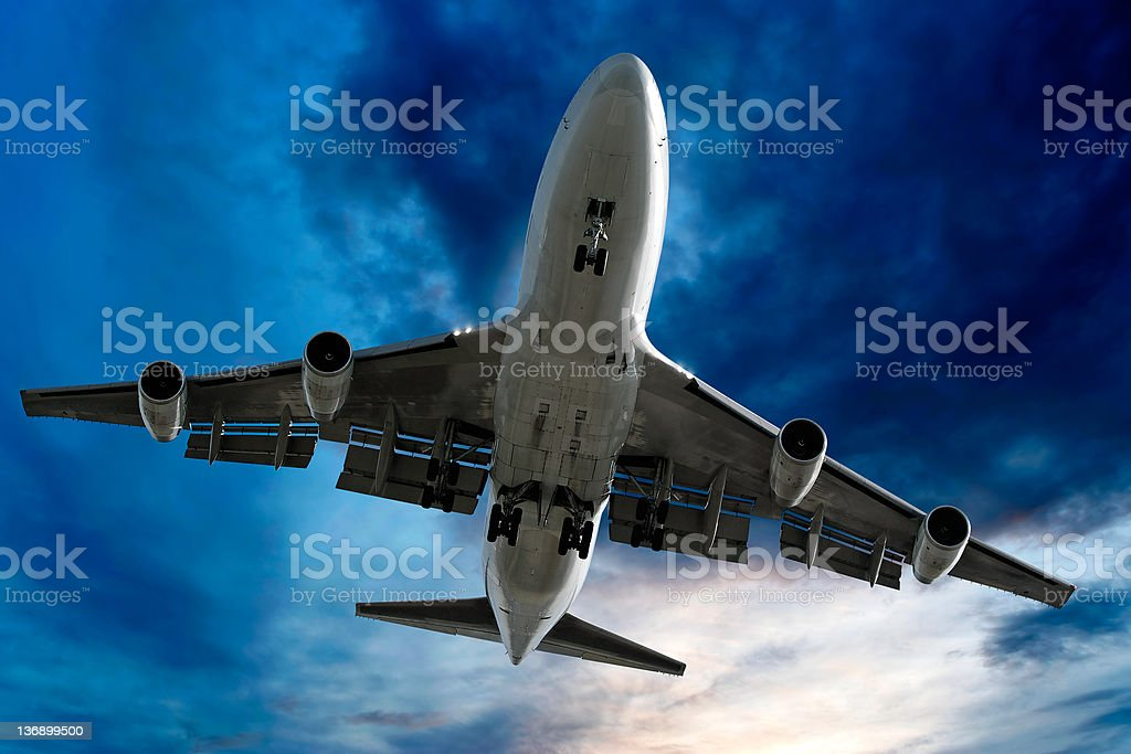 jumbo jet airplane landing at dusk stock photo