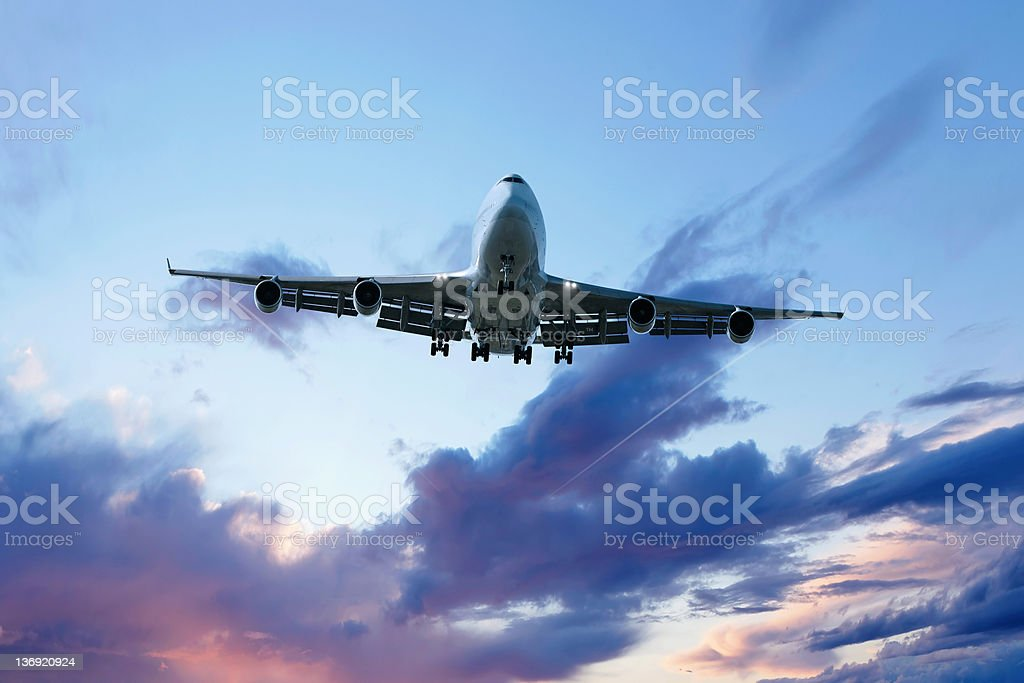 XXL jumbo jet airplane landing at dusk stock photo