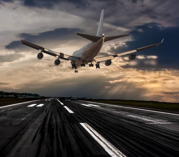 avión a reacción jumbo aterrizaje al atardecer - aterrizar fotografías e imágenes de stock