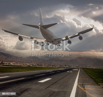 864534880 istock photo Jumbo Jet airplane landing at dusk 664501800