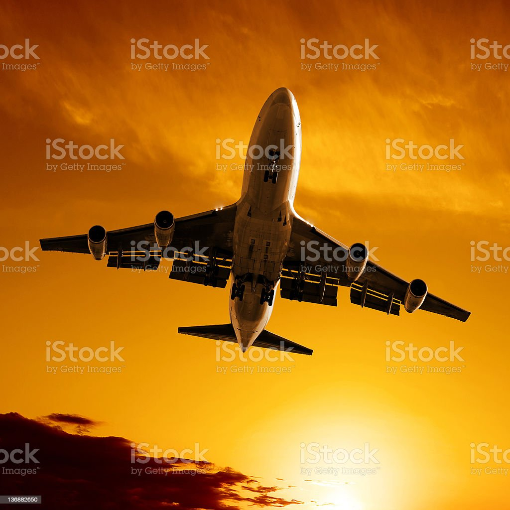 jumbo jet airplane landing at sunset royalty-free stock photo