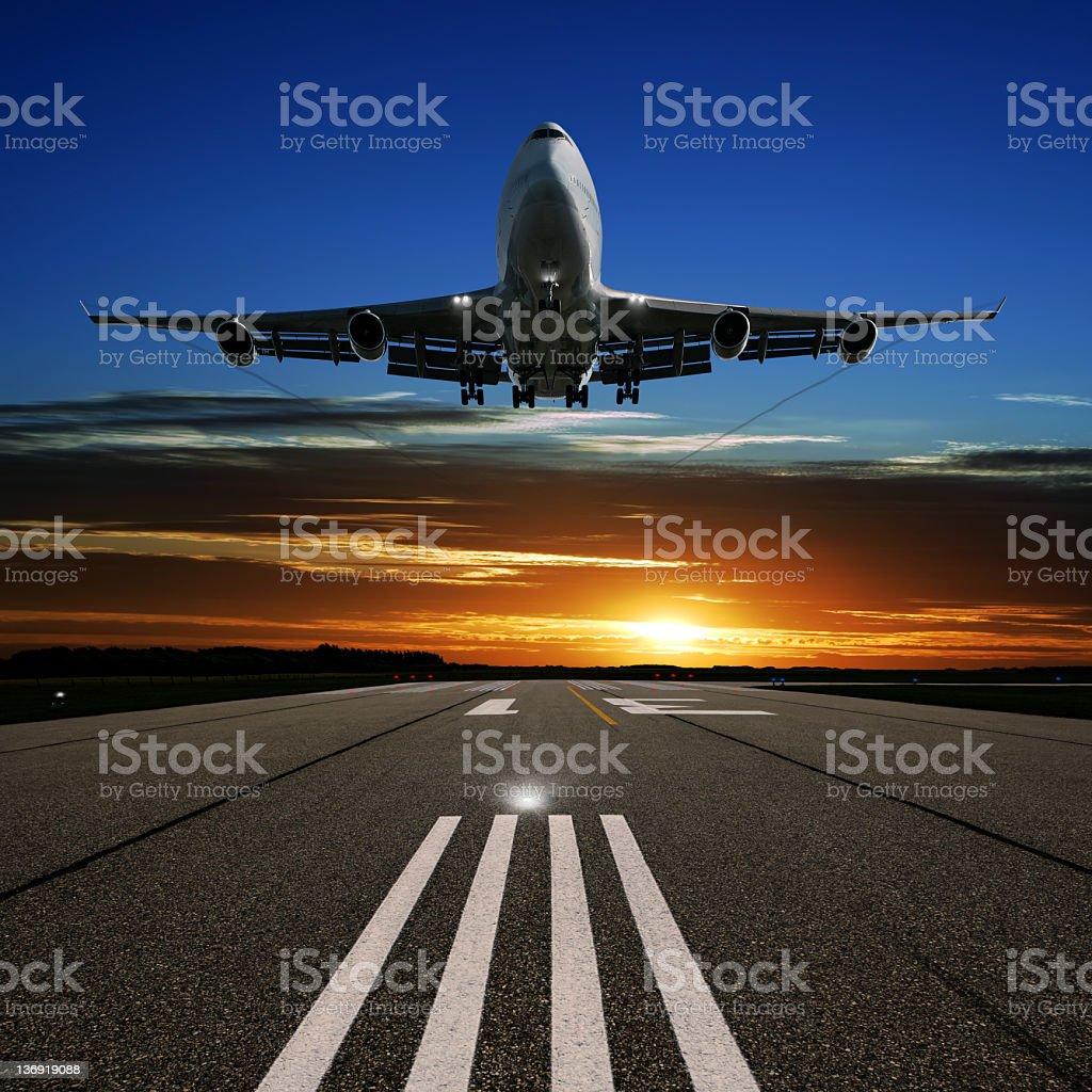 XL jumbo jet airplane landing at sunset stock photo