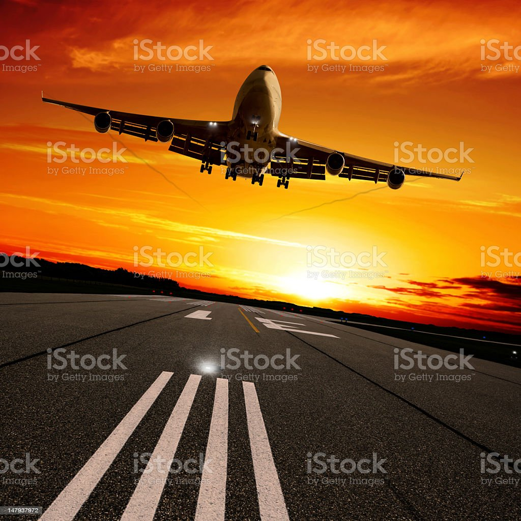 XXL jumbo jet airplane landing at sunset stock photo