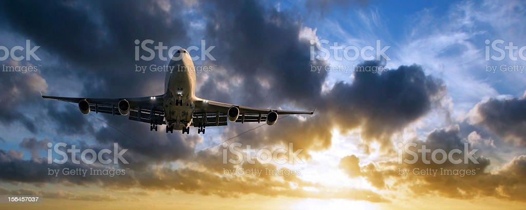 XXL jumbo jet airplane landing at sunset stock photo
