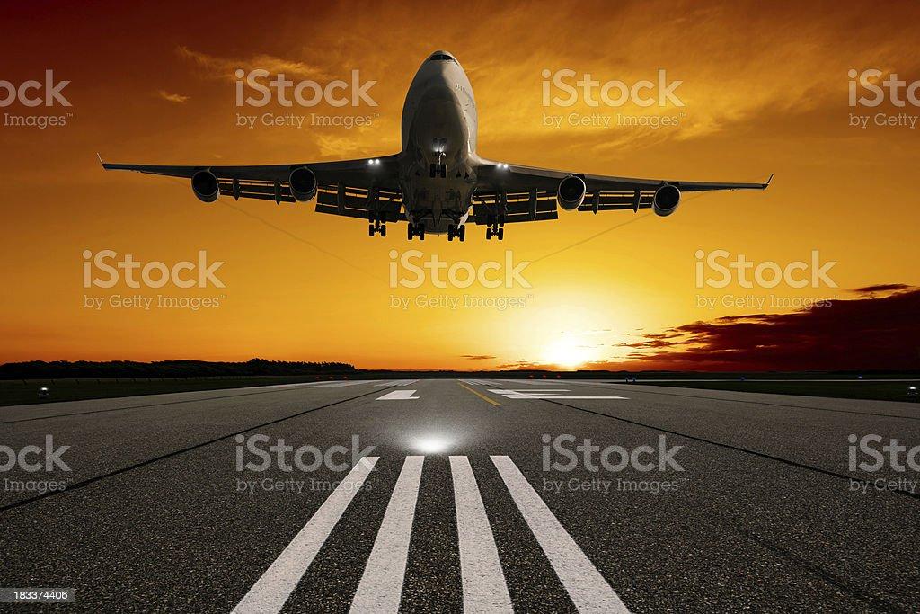 XL jumbo jet airplane landing at sunset royalty-free stock photo