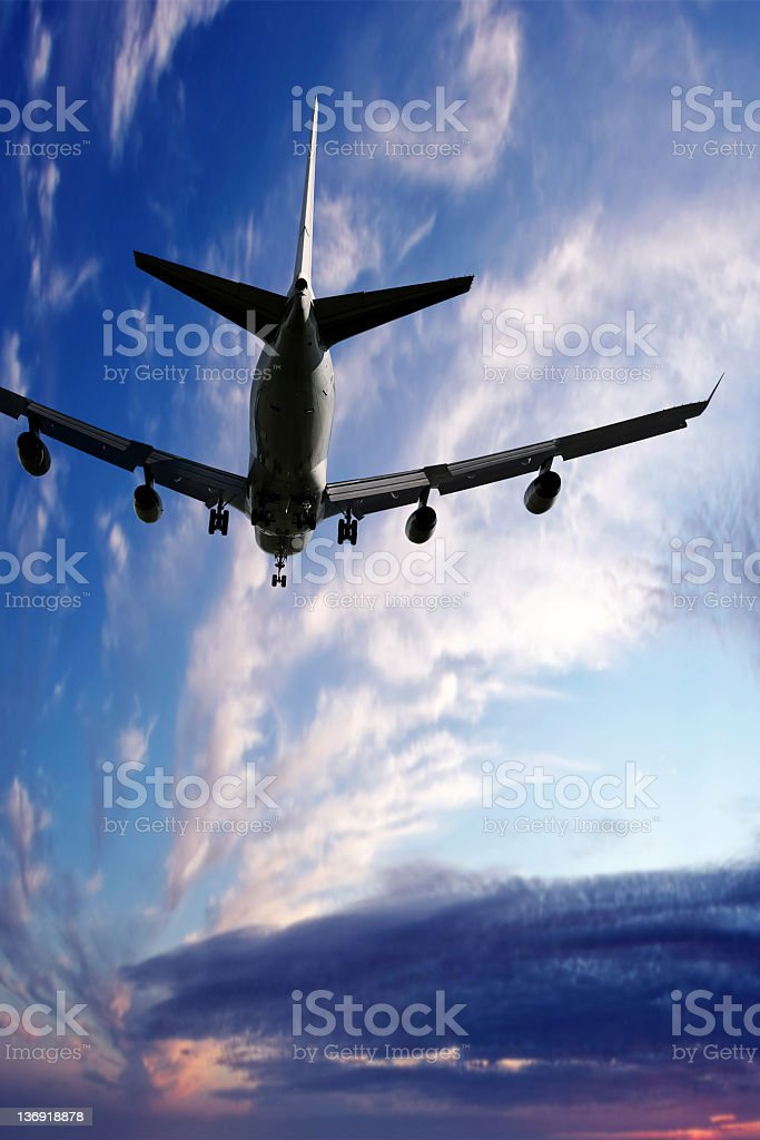 XL jumbo jet airplane landing at twilight stock photo