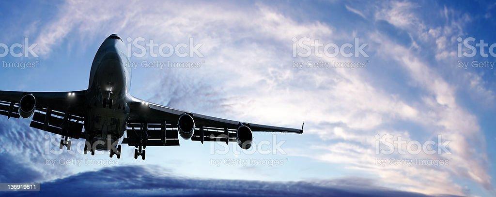 jumbo jet airplane landing at twilight stock photo