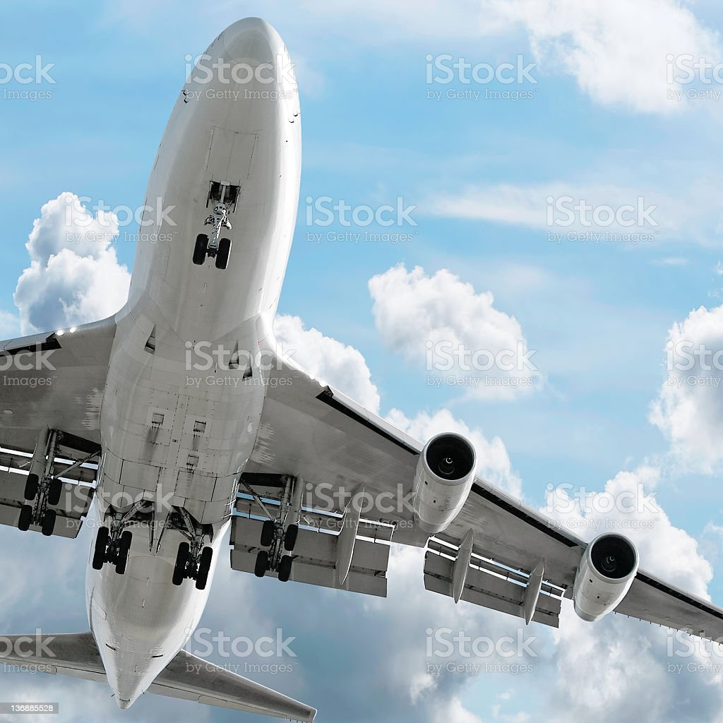 jumbo jet airplane landing in bright sky stock photo
