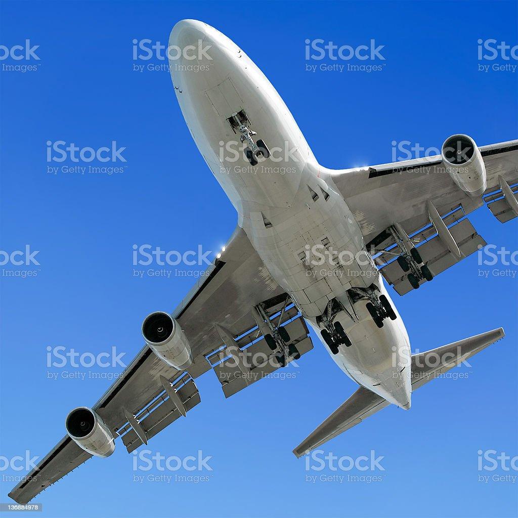 jumbo jet airplane landing in clear blue sky stock photo