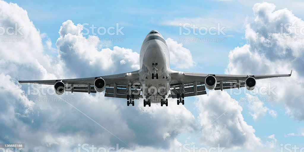 jumbo jet airplane landing in cloudy sky stock photo